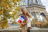 elegant woman on embankment near Eiffel tower showing flag