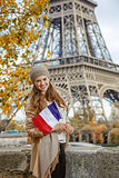 smiling elegant woman on embankment in Paris, France with flag