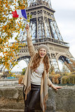smiling tourist woman on embankment in Paris, France rising flag