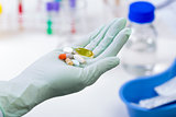 medical pills in a hand of laboratory worker