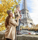 mother and child travelers handwaving on embankment in Paris