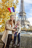 mother and daughter rising flag while sitting on parapet, Paris