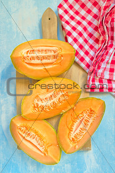 Top view of four slices of cantaloupe melon on table