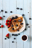 Delicious Crepes Breakfast with Dramatic light over a wood background