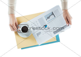 Business woman having a coffee at office desk