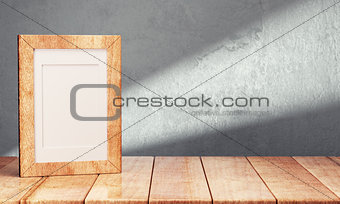 Blank frame on wooden table over gray background