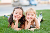 Two little girls in roller skates laying on the grass