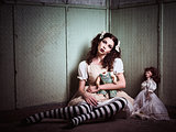 Strange sad girl with dolls sitting in forsaken place