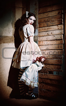 Portrait of weird scary girl with doll in hand