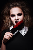 Horror shot: scary evil girl licking bloody knife