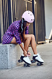 Beautiful young woman put on roller skates and tying shoelaces