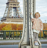 happy child in sport style clothes against Eiffel tower in Paris