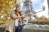 happy mother and daughter taking selfie on embankment in Paris