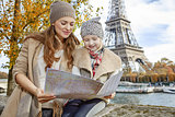 happy mother and daughter tourists looking at the map in Paris