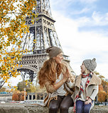mother and child travelers playing on embankment in Paris