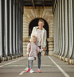 active mother and daughter standing on Pont de Bir-Hakeim bridge