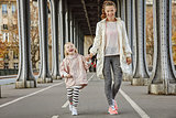 active mother and child on Pont de Bir-Hakeim bridge walking