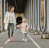 healthy mother and child on Pont de Bir-Hakeim bridge walking