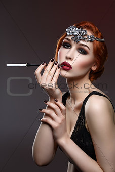 Beautiful girl with smoky eyes and red lips holding cigarette