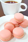Pink Macarons with tea at the background