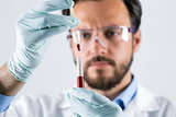 scientist analyzing blood test sample in laboratory