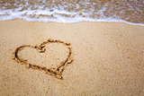 Heart symbol on the sand and sea wave.