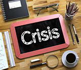 Crisis - Text on Small Chalkboard. 3D Illustration.