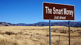 The Smart Money brown road sign