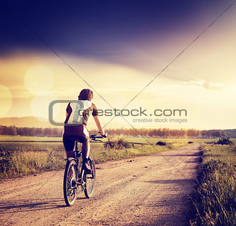 Cyclist Riding a Bike on Country Road. Toned Photo