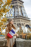 elegant woman with flag on embankment near Eiffel tower in Paris
