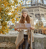 tourist woman on embankment near Eiffel tower looking at map