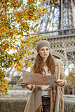 young tourist woman on embankment in Paris, France with map