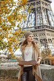 elegant woman holding map and looking into the distance in Paris