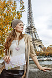 woman with map looking into distance on embankment in Paris