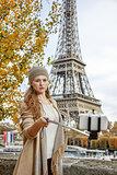 woman taking selfie using selfie stick on embankment in Paris