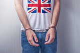 Arrested man with cuffed hands wearing shirt with UK flag