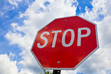Red stop sign on the street, roadside traffic  for stopping.