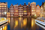 Night dancing houses at Amsterdam canal Damrak, Holland, Netherlands.