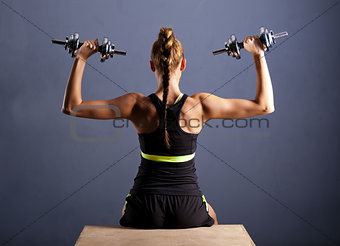 Fit young woman doing shoulder raises with dumbbells, isolated ongray background.