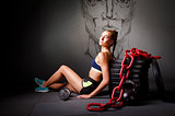 Young attractive woman sit on the flor with sports equipment