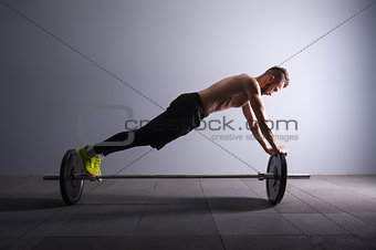 one man exercising fitness plank position on the barbel exercises in studio silhouette dark key