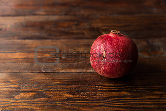 One red and ripe pomegranate lying on the dark wooden table