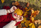 Red hair girl lying with autumn maple leaf