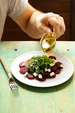 chef prepares salad of boiled beets, cheese and arugula