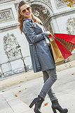 happy trendy woman in trench coat shopping in Paris, France