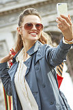 happy elegant woman shopper in Paris taking selfie with phone