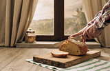 Man cutting a loaf of fresh bread