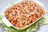 Pasta casserole with bacon, ham, cheese and tomato