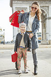 smiling mother and child with shopping bags in Paris, France