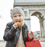 child near Arc de Triomphe eating French macaroon